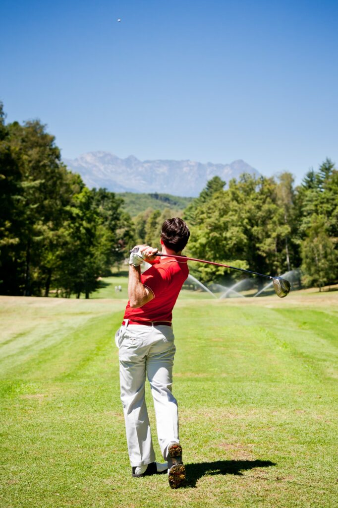 Golf player performs a tee shot using a driver club.