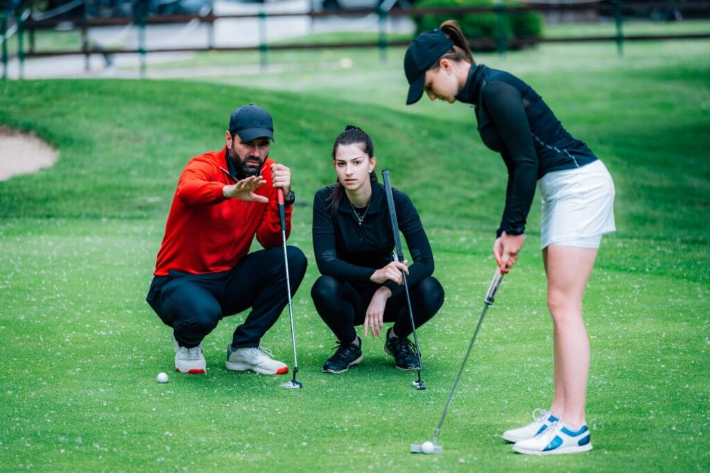 Golf putting lesson, two young female golfers practicing putting with golf instructor