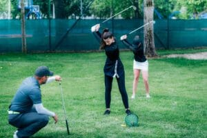 Golf swing technique – golf instructor working with two young ladies on a golf range